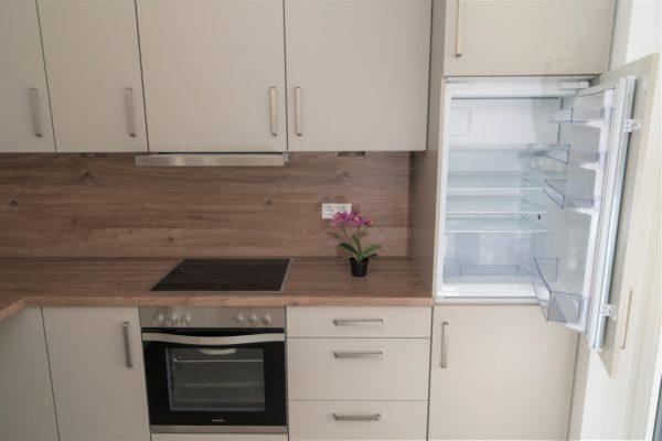 Küche der Musterwohnung inklusive Ansicht des offenen Kühlschranks