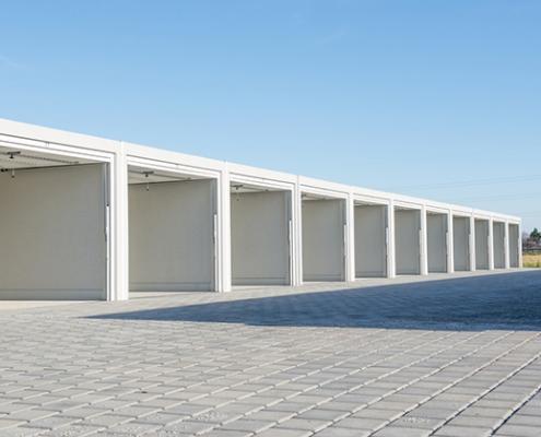 Zeigt ein Gelände mit offenstehenden Garagen darauf.