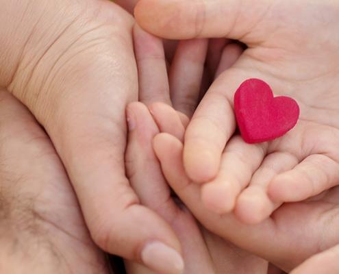 Hände einer Familie halten gemeinsam ein rotes Herz