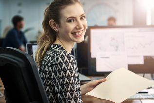 537266772_Arbeit_Büro_Frau_lachen_Assistenz_Computer_Unterlagen_Arbeitsplatz_jung